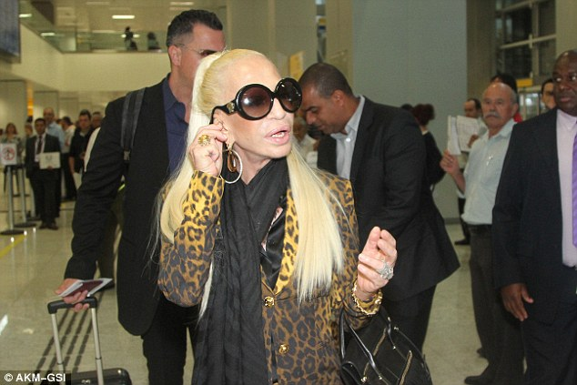 High-class: Donatella was decadently dressed for her trip, in a loud leopard print trouser suit and thick black scarf